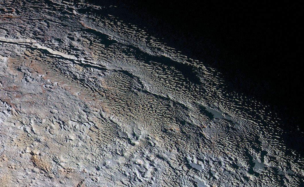 The Tartarus Dorsa mountains rise up along Pluto's day-night terminator and show intricate, puzzling patterns of blue-gray ridges and reddish material in between.