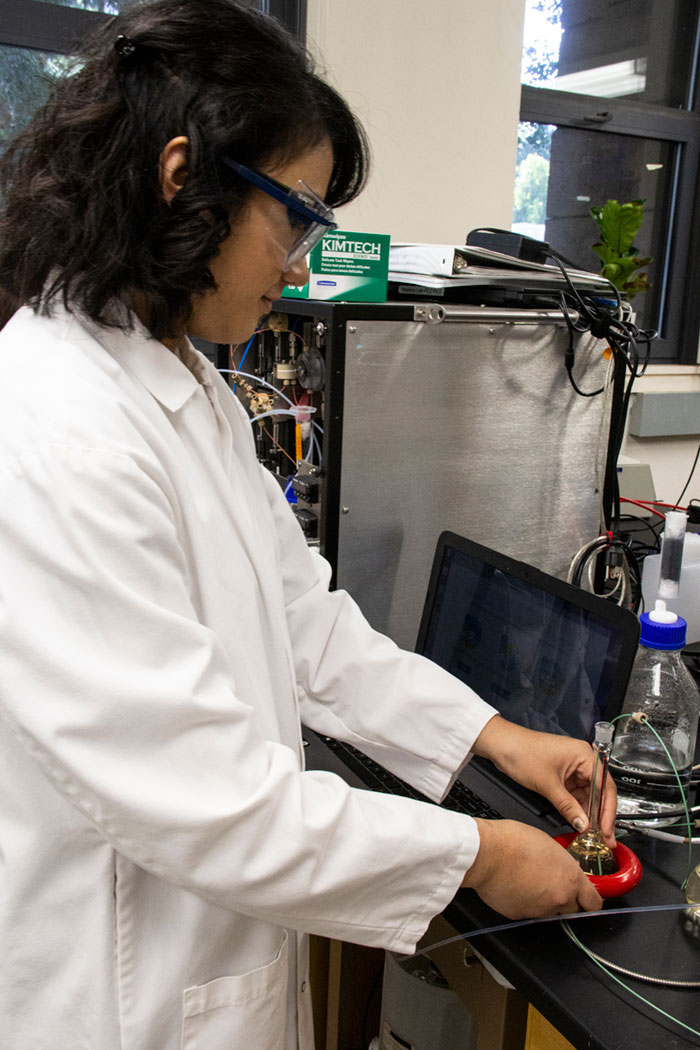 Student in lab coat works with testing device.