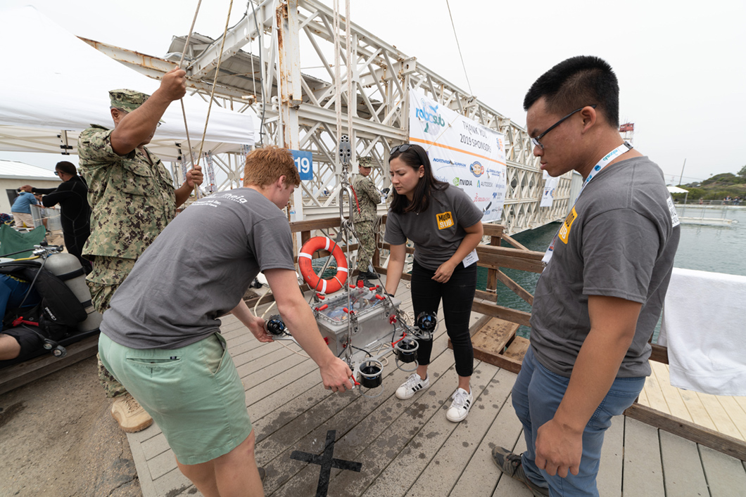 Students move robot sub with crane.