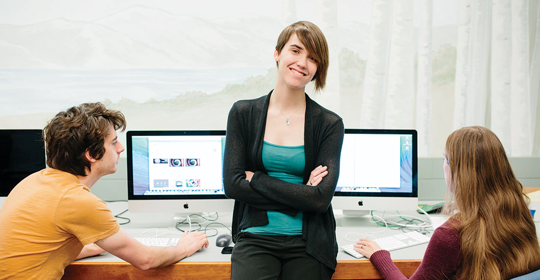 Elly Scholfied stands in front of computer monitors with a student either side of her.