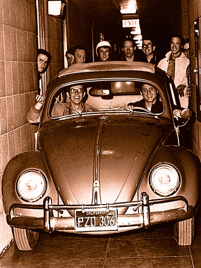 VW Beetle squeezed in narrow hallway surrounded by laughing students.