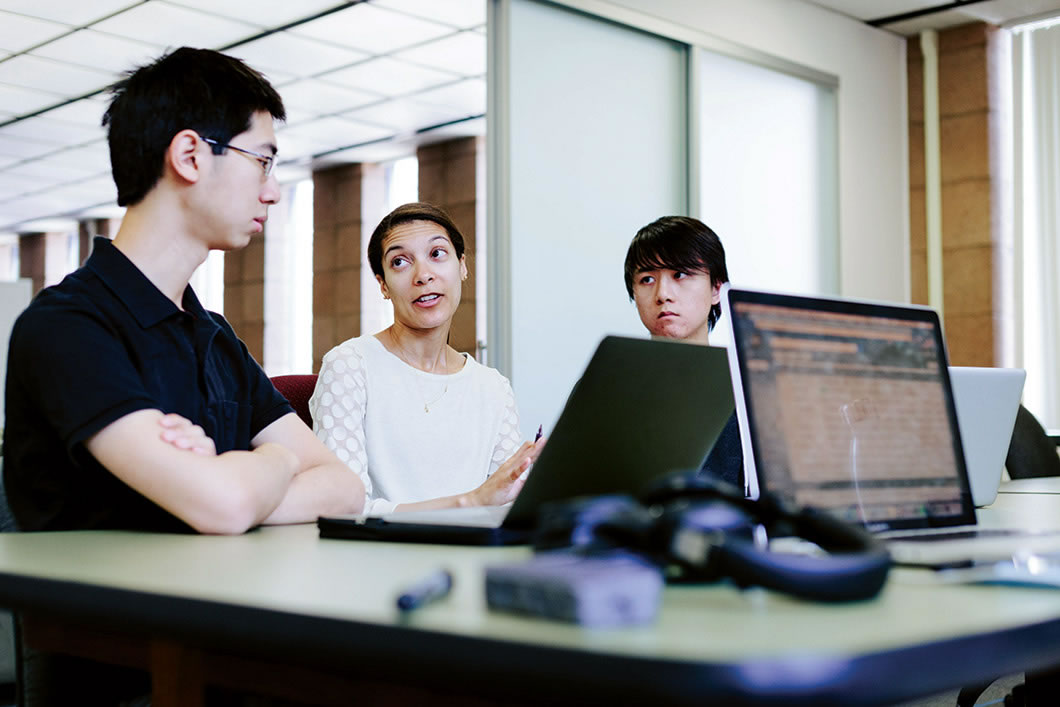 Three people talking in front of a laptop.