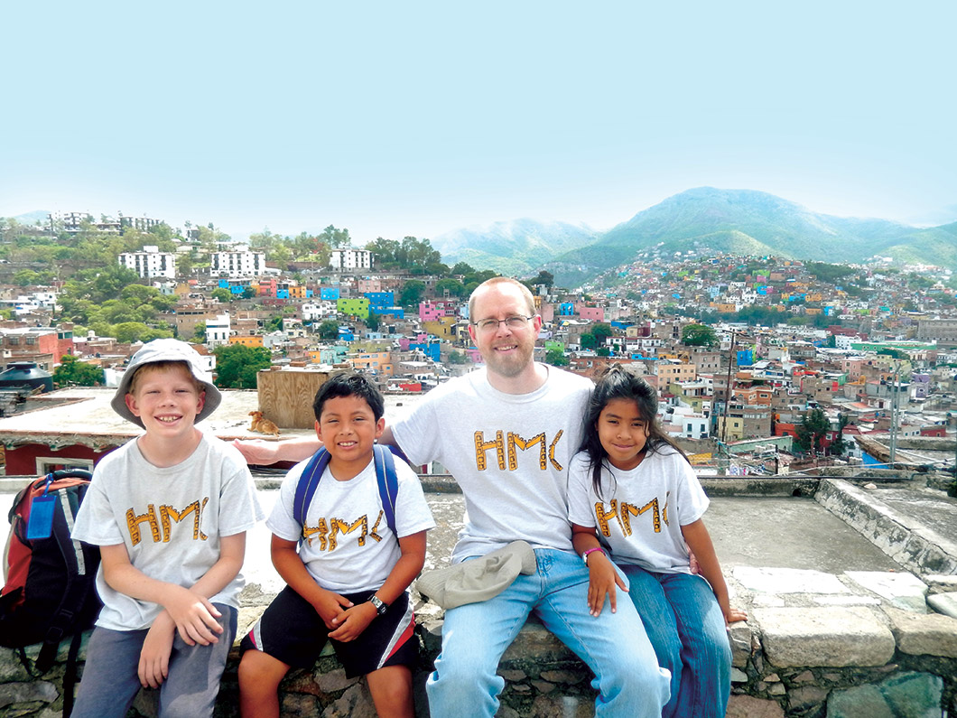 David Vosburg and children sitting on wall overlooking city.