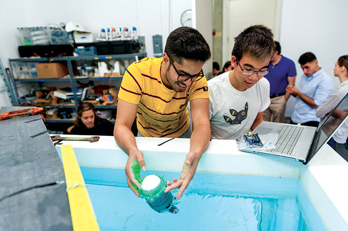 Two students test device in water tank.