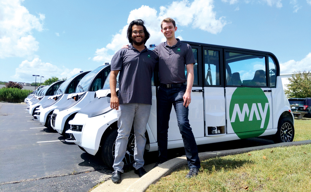 Aman Fatehpuria and Sean Messenger in front of May Mobility self-driving vehicles.