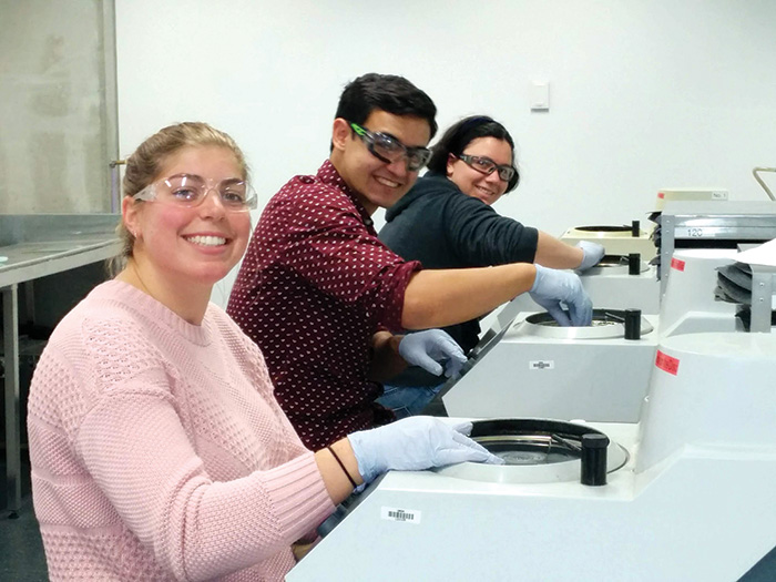 Three students at wearing gloves working on samples in testing machines.