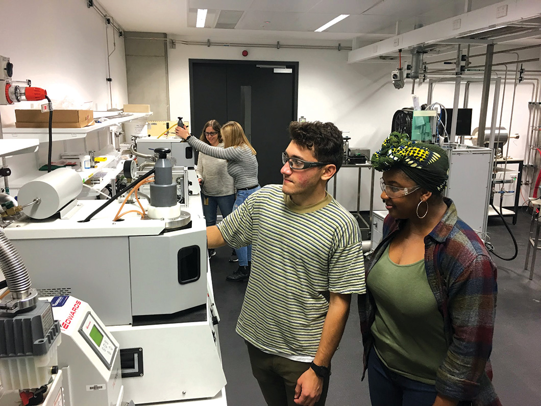 Four people in lab working with testing machines.