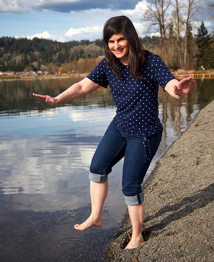Julia with jeans rolled up stands poised to step in a pond.