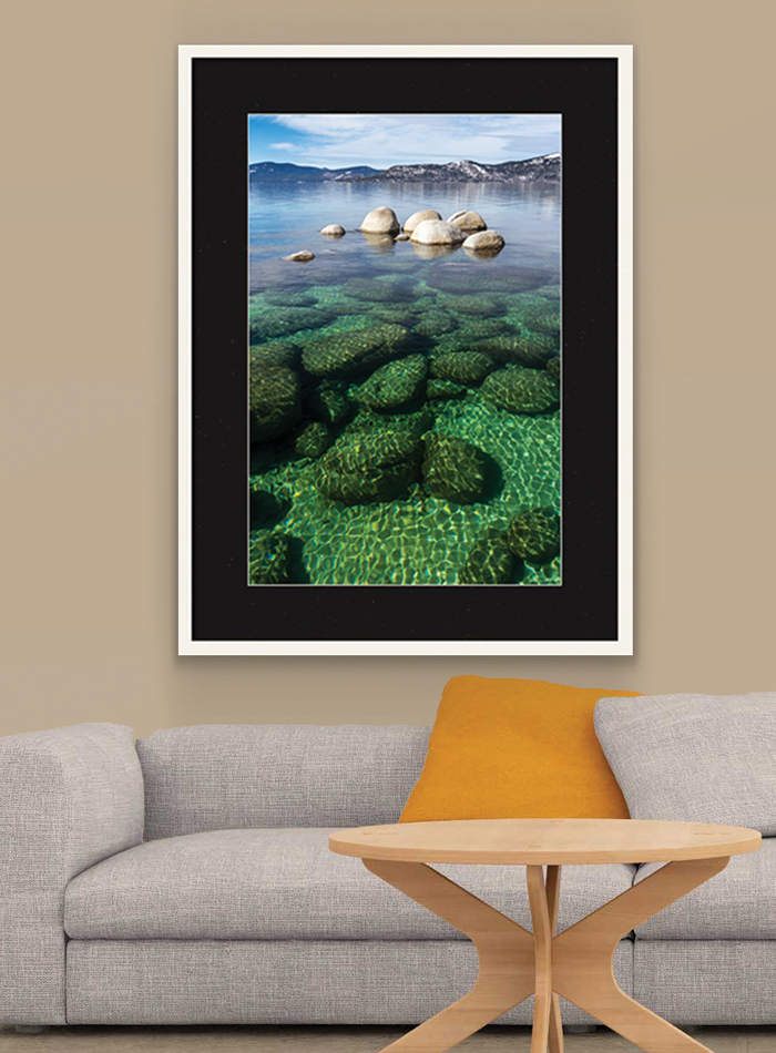 Lake photo in frame on wall over couch.